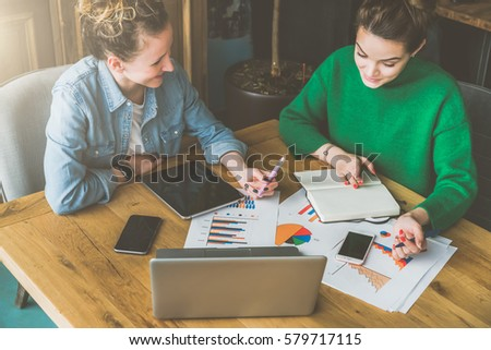 Teamwork. Two smiling young business women sitting in office at table and working. On table is laptop, smartphone, tablet, paper charts and notebook. Students learning online, chatting. Brainstorming. #579717115