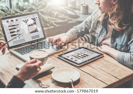 Teamwork,two young business women sitting at table,drinking coffee and working online.First girl is showing pen on chart and diagram on computer screen.On table tablet PC.Students are learning online.