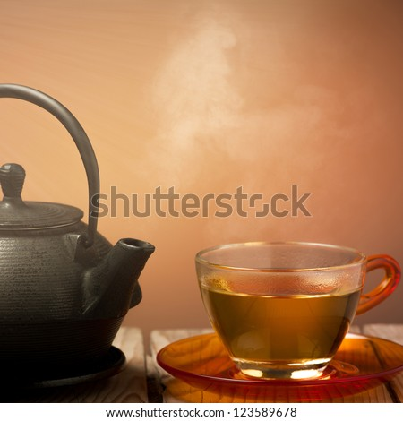 Teapot and a cup of tea on an old wooden table - hot steam smoking from cup of tea