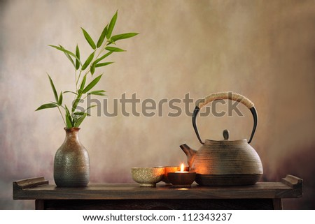 Teapot and cup with burning candle.