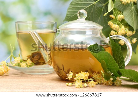 teapot and cup with linden tea  and flowers on wooden table in garden - stock photo