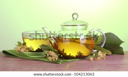 teapot and cup with linden tea and flowers on wooden table on green background - stock photo