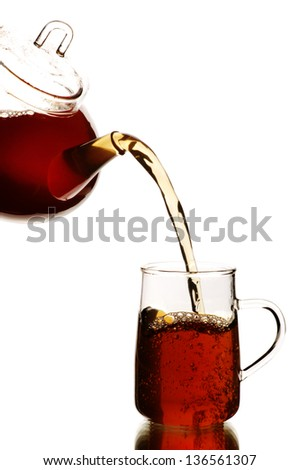 Teapot and tea glass with black tea, isolated on white