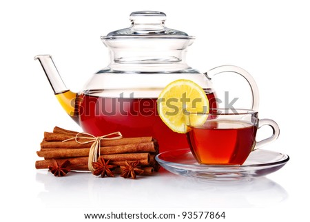 Teapot and tea in cup with spices and lemon isolated on white background