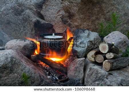 Teapot on campfires amongst stone