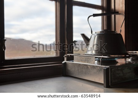 Teapot on the gas cooker in a hut