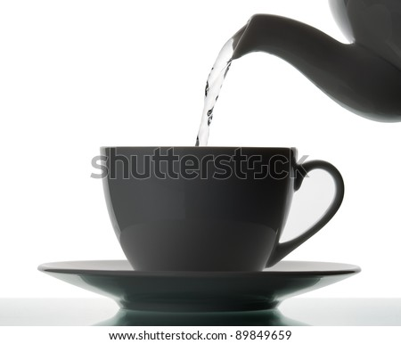 Teapot pouring boiling water into a cup. Silhouette