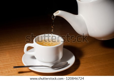 Teapot pouring tea into a cup on a wood surface