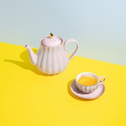 Teapot with cup of tea on multi colored pastel blue and yellow background. Minimal herbal organic beverage concept. Trend shadows.