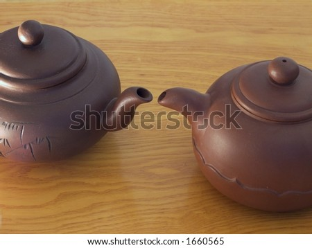 Teapots, lips close to each other.