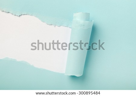 Tear in a piece of blue paper revealing white background underneath  Stockfoto ©