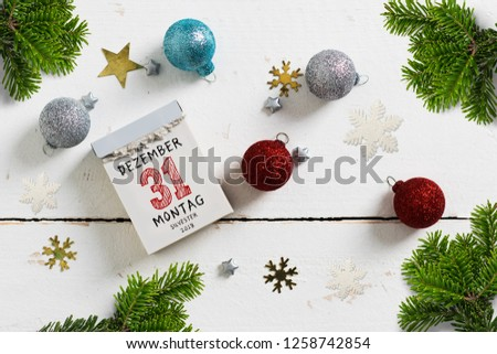 tear-off calendar with 31st of december 2018, silvester (in German) on top surrounded by christmas decoration on white background #1258742854