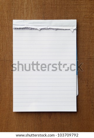 tear paper note on wood texture background