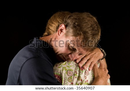 Tearful hug - man and woman have emotional embrace, suggestive of grief, relationship crisis, or reconciliation.