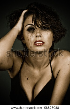 Tearful woman in black dress posing in studio