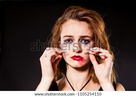 Tearful young woman holds false eyelashes.