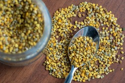 teaspoon full of bee pollen, on a table with scattered pollen granules, next to a vase, out of focus, of glass full of granules, dark wooden table background