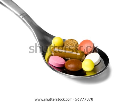 Teaspoon with pills isolated on white background
