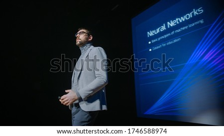 Tech Conference Stage: Speaker Talks about Product. Neural Networks, Artificial Intelligence, Big Data and Machine Learning. Screen Shows Infographics, Statistics. Live Startup Business Event