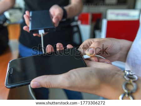 Tech Device Charge Sharing.woman and man hands connecting a white lightning charging cable to digital black phone. Generation Z, people and technology concepts.