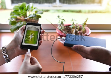 """Tech Device Charge Sharing.woman and man""""s hand connecting a white lightning charging cable to digital black phone. Generation Z, people and technology concepts."""