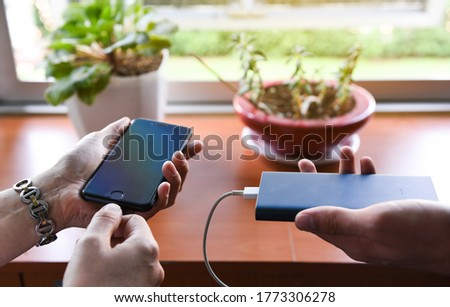 Tech Device Charge Sharing.woman and mans hand connecting a white lightning charging cable to digital black phone. Generation Z, people and technology concepts.
