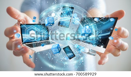 Tech devices connected to each other by businessman on blurred background 3D rendering #700589929