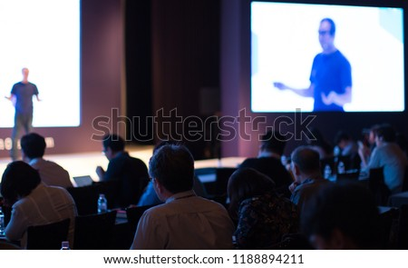 Tech Presenter on Stage Giving Presentation Speech at Conference Seminar. Innovation and Growth Speaker Giving Lecture at Meeting. Audience Watching Presenter. White Screen Background