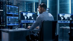 Technical Controller Working at His Workstation with Multiple Displays. Displays Show Various Technical Information. He's Alone in System Control Center.