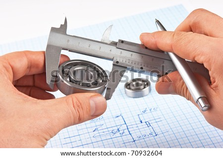 Technical drawing and callipers with bearing in hand on graph paper