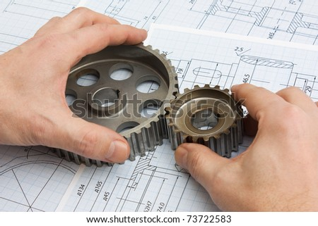 technical drawing and pinion gears in hands
