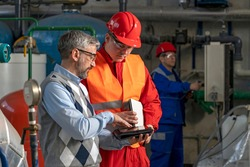 Technical Manager Using Digital Tablet and Discussing About Production Process with Power Plant Worker. District Heating Power Plant. Digital Technology and Teamwork Concept. Industry 4.0