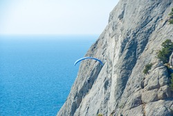 Technical parachute sports photography, blue parachute on the background of rocks and the sea, Parasailing, also known as parascending or para kiting