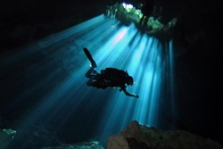 Technical scuba diver exploring underwater cenote. Scuba diver in the sun light from the water surface. Underwater dark cave and diver.