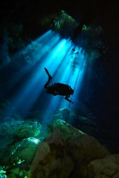Technical scuba diver in the dark cave with sunbeams. Underwater photography from speleology and deep diver exploring the dark cenote. Sun rays underwater. Cave scuba diving.