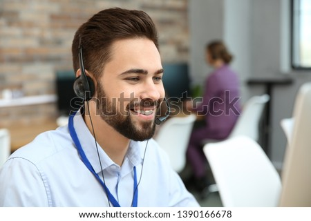 Technical support operator working with headset in office