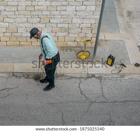 technical with water leak detector on a road of on city. These detectors are an important tool to detect the sound of leaks in noisy cities.