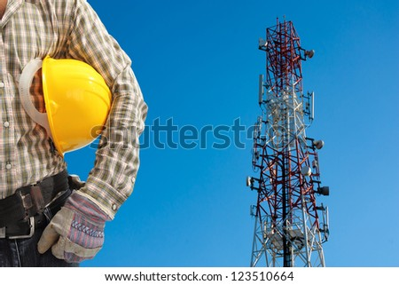 technician against telecommunication tower, painted white and red in a day of clear blue sky.