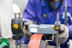 Technician aligning shaft with Laser Shaft Alignment tool. Shaft alignment is the process of aligning two with each other to within a tolerated margin. Selective focus.