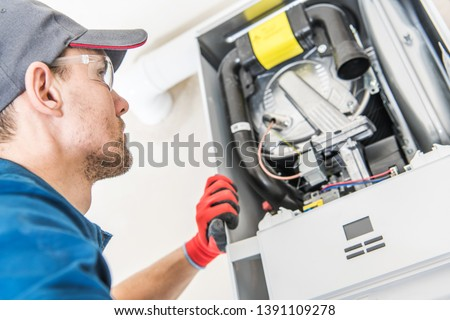 Technician and the Heater Issue. Caucasian Worker Looking Inside Central Gas Heater Trying to Fix the Problem. ストックフォト ©