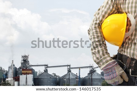 technician at work against corn dryer silos and blue sky background #146017535