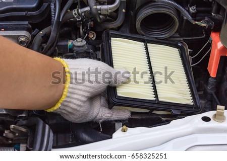 Technician change a new car air filter, Put new wet air filter on car engine #658325251