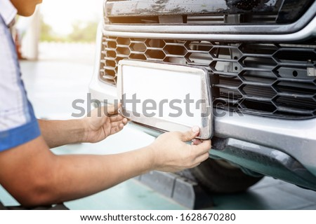 Technician changing Thailand car plate number in service center ストックフォト ©