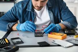 Technician checking broken smartphone at table in repair shop, closeup