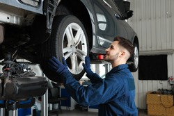 Technician checking car on hydraulic lift at automobile repair shop