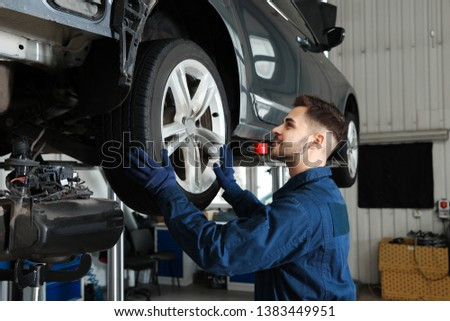 Technician checking car on hydraulic lift at automobile repair shop #1383449951