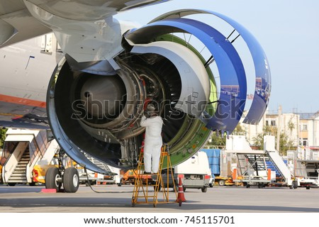 Technician checking engine of civil airliner.