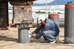 Technician checking graph last ten blow of spun pile driving from hydraulic drilling machines on construction site