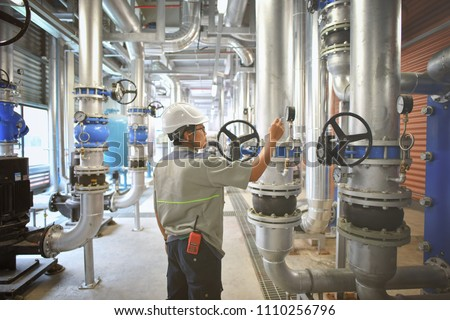 Technician checking list status vacuum pump and valve gate chiller system for chiller room in factory