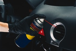 Technician cleaning the air conditioning vents with spray. Maintenance and repair concept of the air conditioning and heating piping system. Workshop topic and car repairs. Automobile dashboard.